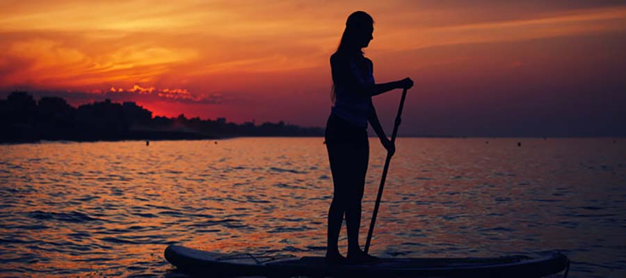 Silhouette of standup paddle boarding performed by girl